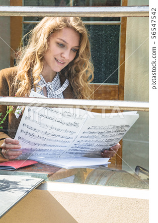Girl sitting in cafe and reading musicians notes 56547542