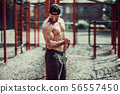 Fitness man exercising with stretching band in outdoor gym. 56557450