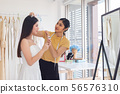 asian bride trying on wedding dress in a shop with 56576310