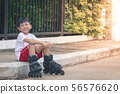 Boy asia sitting smiling at rollerblade shoes 56576620