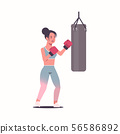 woman boxer doing exercises with punching bag making direct hit in red boxing gloves attractive 56586892