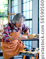 Old Asian craftsman act as measurement of wood 56590560