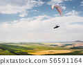 A paraglider flies in the sky in a cocoon suit on a paraglider over the Caucasian countryside with 56591164