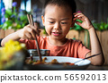 Asian child having lunch at the restaurant 56592013