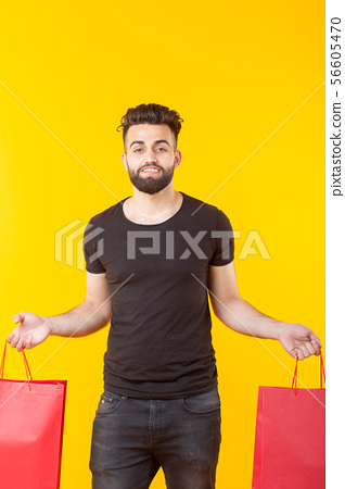 Man is holding red shopping bags on a yellow background. The concept of shopping in the supermarket 56605470