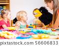Kindergarten teacher and children playing with hand puppet 56606833
