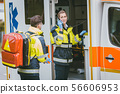 Medics in front of ambulance talking to headquarters using radio 56606953