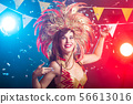Carnival, belly dance and holiday concept - Beautiful female samba dancer wearing gold costume and 56613016
