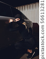 Masked robber woman car The thief is levering the lock at the door car robbery. 56613281