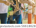 Tourists try to use a bow and arrow and shoot  56618628
