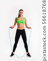 Portrait of muscular young woman exercising with jumping rope on white background. 56618768