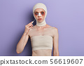 young woman in bandages holding a scalpel near her face 56619607