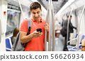 Man is looking on phone in the train 56626934