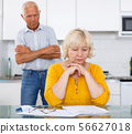 Unhappy senior woman sitting with documents, qurrel with husband 56627018
