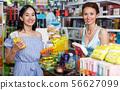 Lucky woman seller helping to girl customer 56627099