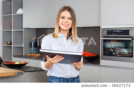 Portrait of smiling attractive girl holding book while standing in stylish interior of home kitchen 56627173