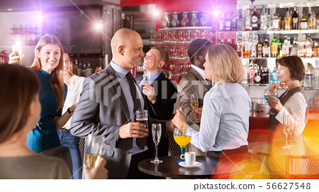 Man talking to woman on corporate party 56627548