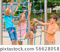 Children are climbing on the grid 56628058