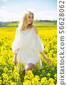 Young female posing in yellow oilseed rape field wearing in white dress 56628062