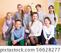 Friendly group of pupils with teacher in schoolroom 56628277