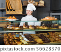 Glad female cooks demonstrating and selling to the customer pastry 56628370