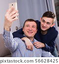 Man with his adult son are taking selfie together 56628425