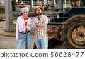 Farm family near farming equipment 56628477