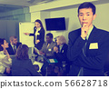 Thoughtful Korean man standing at office on background with working colleagues 56628718