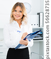 Young girl with folder of documents is standing in modern office 56628735