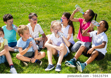 Happy children drinking water after running in park outdoors 56628794