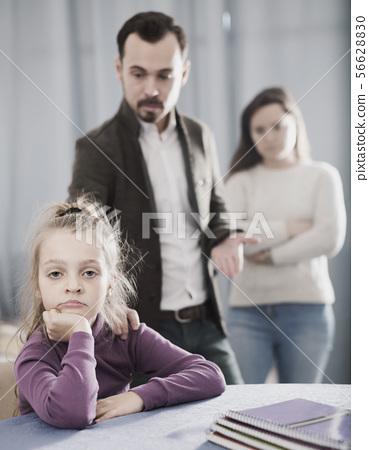 Ordinary parents lecturing girl for bad behavior 56628830
