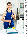 Female office cleaner is satisfied after cleaning 56629217