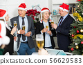 Colleagues celebrating Christmas in office 56629583