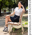 Attractive brazilian girl sitting on a bench in summer park 56629919