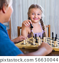 children at chess board indoors 56630044
