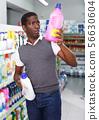 African man choosing household chemicals 56630604