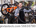 man in apron considering composition of wheel for bicycle 56630780
