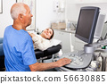 Mature male doctor using ultrasound scan examining female patient in modern hospital 56630885