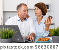 Positive senior man and woman with phone at laptop in home interior 56630887