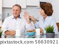 Unhappy mature couple discussion while quarrel in home interior 56630921