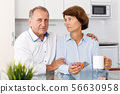 Unhappy mature couple sittimg at kitchen table and taking drugs in home 56630958
