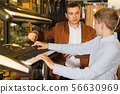 Teenage boy and father choosing best keyboard in musical shop 56630969