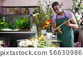 Man creating floral arrangement with gerberas 56630986