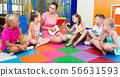 Kids listening positive teacher playing small guitar 56631593