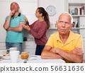 Upset senior man sitting at table, family couple quarrelling 56631636