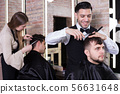 Male hairdresser cutting hair of male client 56631648