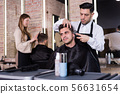 Hairdresser man doing styling of guy with electric hair clipper 56631654