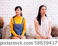Displeased Asian females sitting on sofa 56639417