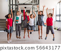 A group of cheerful small school kids in corridor, jumping. 56643177