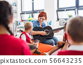 A group of small school kids and teacher with guitar sitting on the floor in class. 56643235